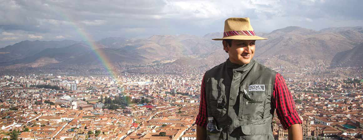 expert peru guide fabricio with cusco city rooftops behind him