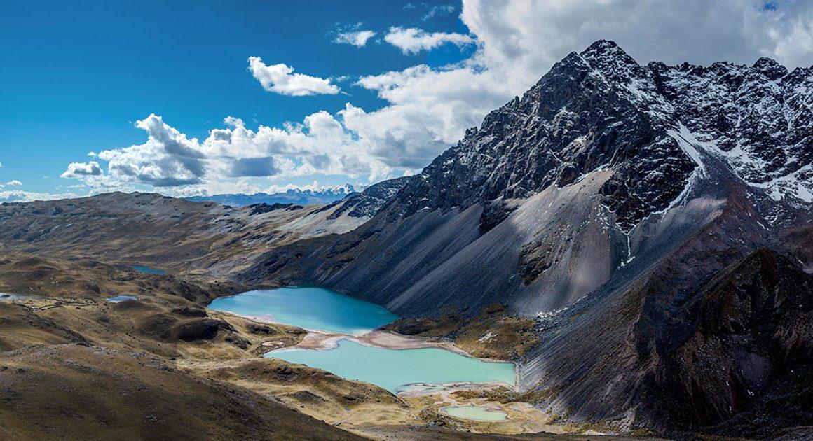 a view of a light blue laguna next to a mountain on the Ausangate trek