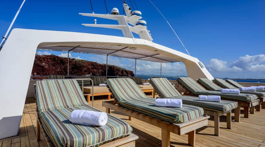 Reclined beach chairs on the deck of the Seaman Journey, a catamaran offering Galapagos cruises.