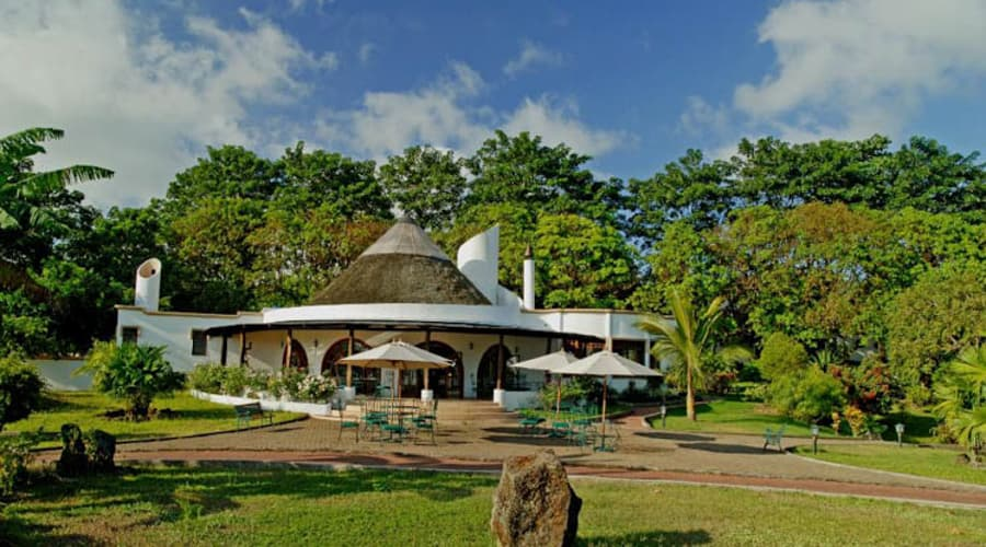Trees surround the 5-star Royal Palm Hotel with white walls and wooden details on the Galapagos Islands.