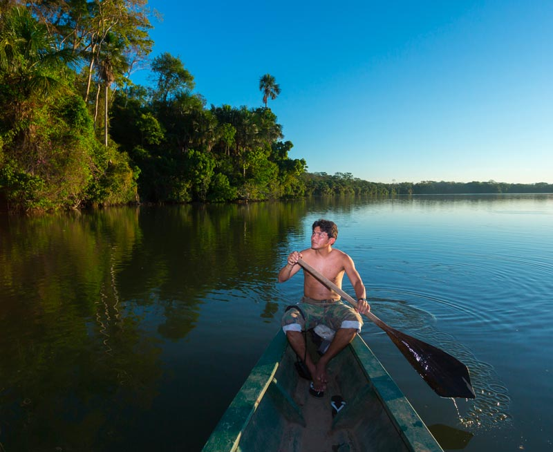 A man rows a boat on a river in the Amazon Rainforest with lush green trees growing on the shore.
