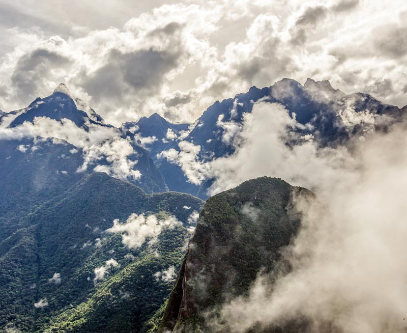 Mountains covered with lush green vegetation pierce the rolling clouds above in the Andes Mountains.