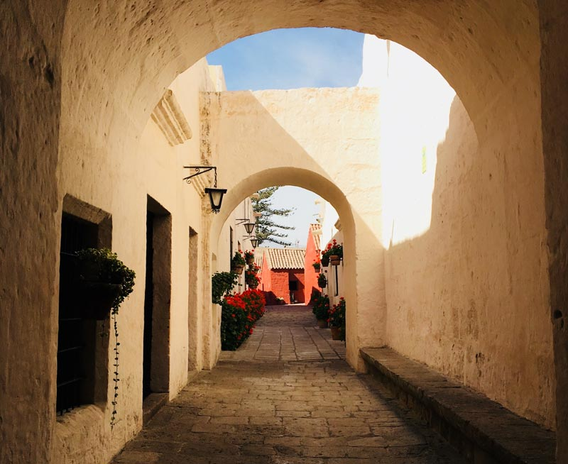 White arches above the entrance to Santa Catalina Monastery with a glimpse of red buildings inside.