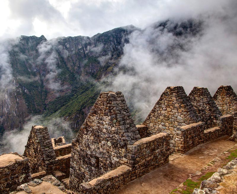 Close up of stone walls with pointed tops at Machu Picchu with cloudy, mountain terrain behind.