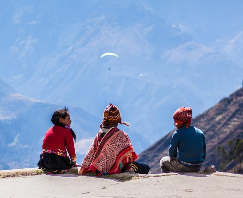 Three children in traditional clothing overlooking a mountain landscape with a paraglider above.