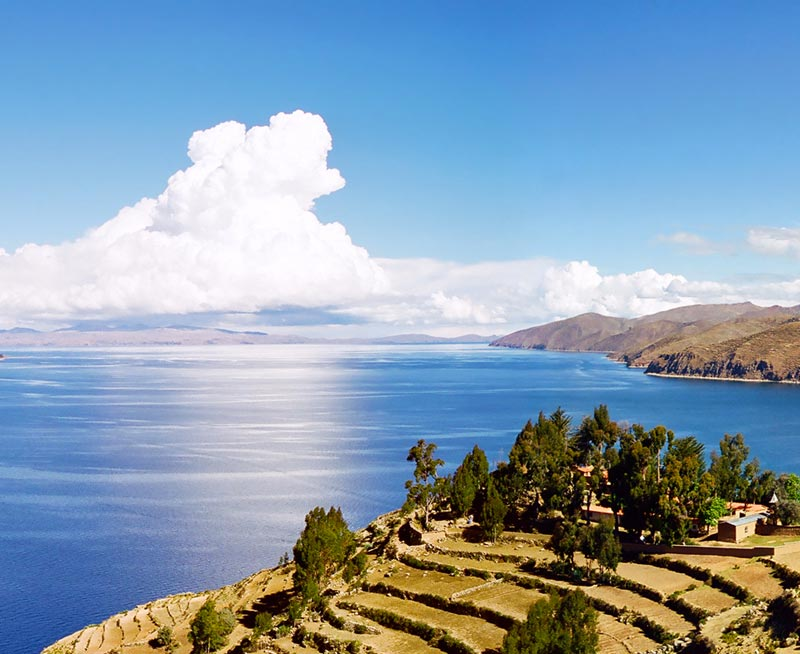 An island with terraced land and small houses overlooks Lake Titicaca and another island's shore.