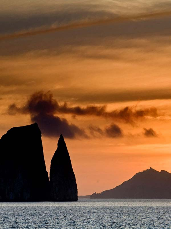 A yellow-orange sunset silhouettes Kicker Rock, a jagged rock formation jutting out of the ocean in the Galapagos.