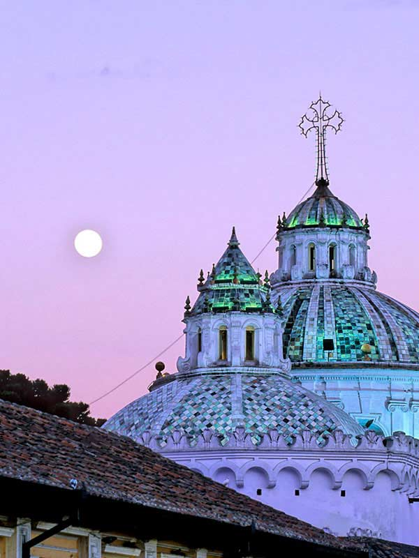 The full moon is seen next to two green church domes of the Metropolitan Cathedral in Quito Ecuador.